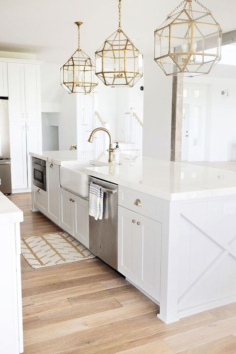 all white kitchen with gold geometric pendant lighting, light wood floors and oversized center island with farmhouse sink