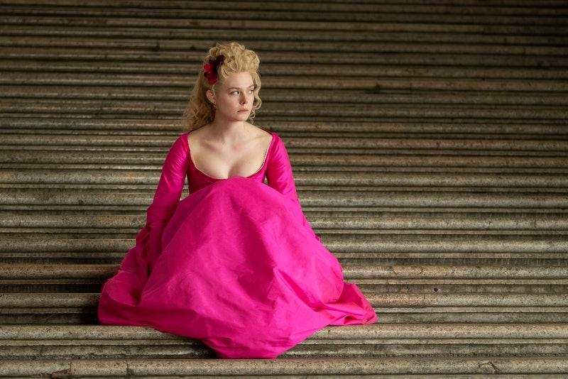 The Great (2020). Catherine is sitting alone on a set of grey stone steps, seemingly outside. She is wearing a fuchsia coloured dress, the skirt bunched up with her knees drawn up to her chest. She hair is in an elaborate curly updo with matching pink flowers affixed to one side above her ear. Catherine looks very disgruntled, gazing off to one side.