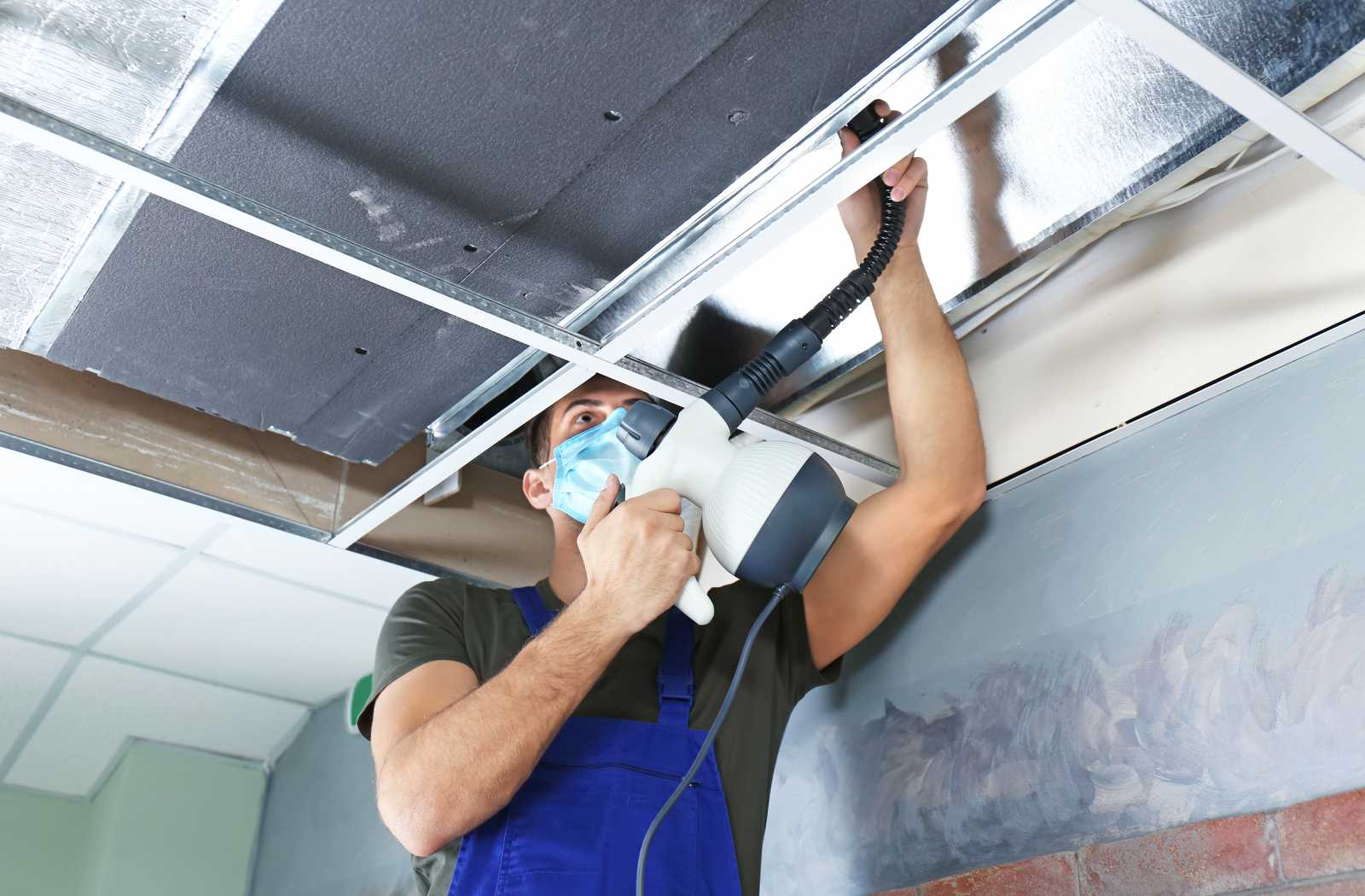 Technician in blue coveralls cleaning a home's ductwork