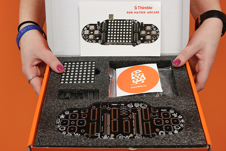 An Thimble kit box is held by two hands, open, and displaying the components and instruction cards for the RGB Matrix Arcade STEM kit.