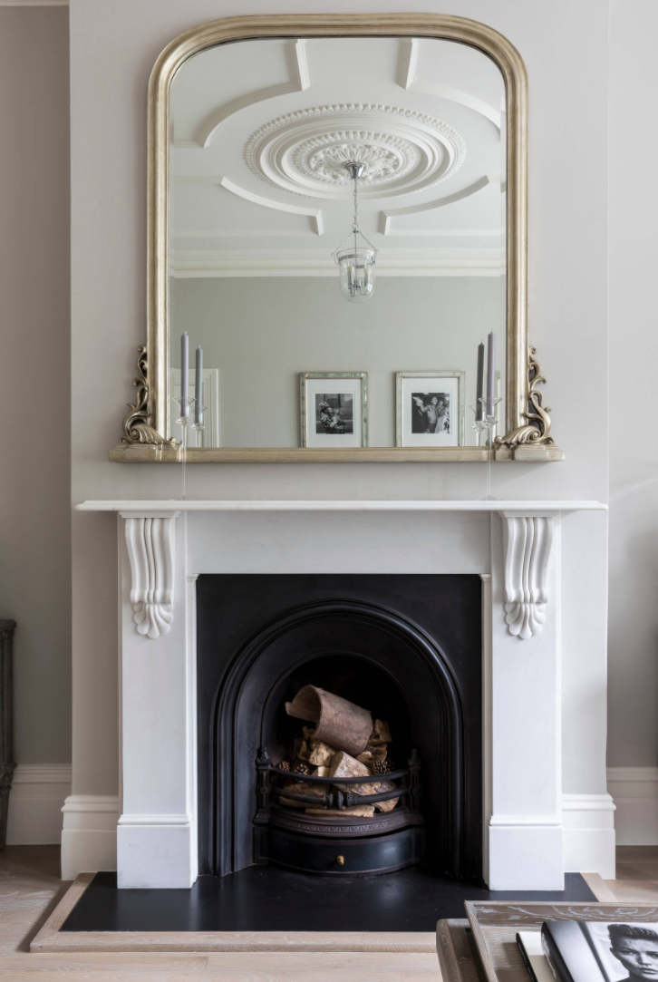 Fireplace and a mirror reflecting ceiling cornices (ceiling skirting) in a period property.