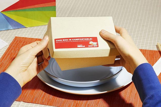 Hands holding a Notpla takeout food container over a bowl and plate on a placemat and writing that says this box is compostable.