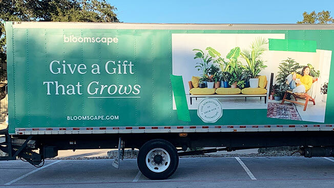 "Green Bloomscape truck side ad with pictures of plants and the message ""Give a gift that grows"""