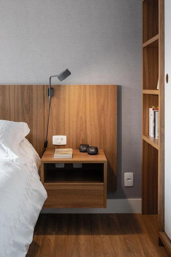 Quarto com cabeceira de madeira com criado mudo e piso de madeira.