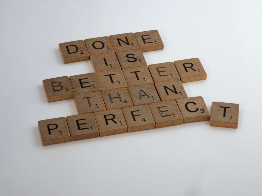 "scrabble pieces spelling ""done is better than perfect"""