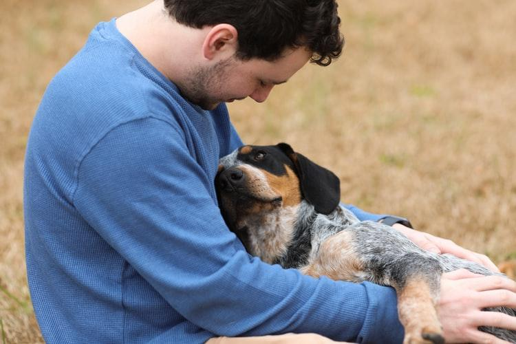 man snuggling with dog