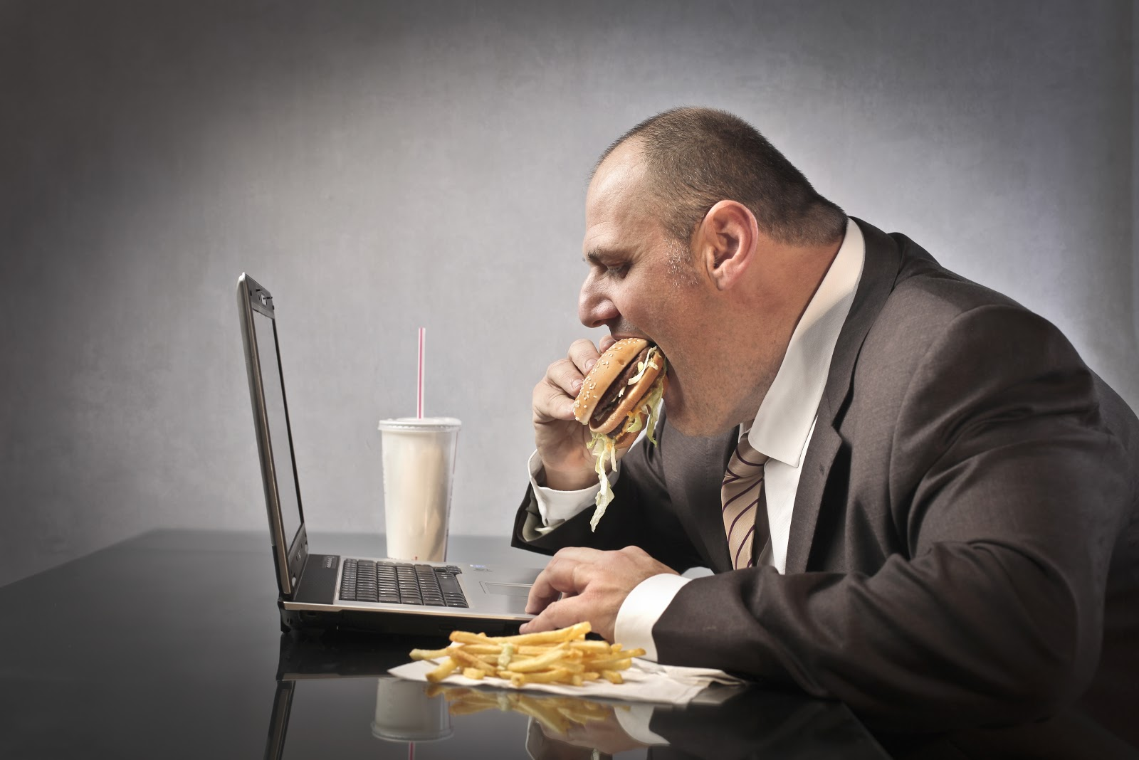 A businessman in a suit using a computer while eating a cheeseburger and fries