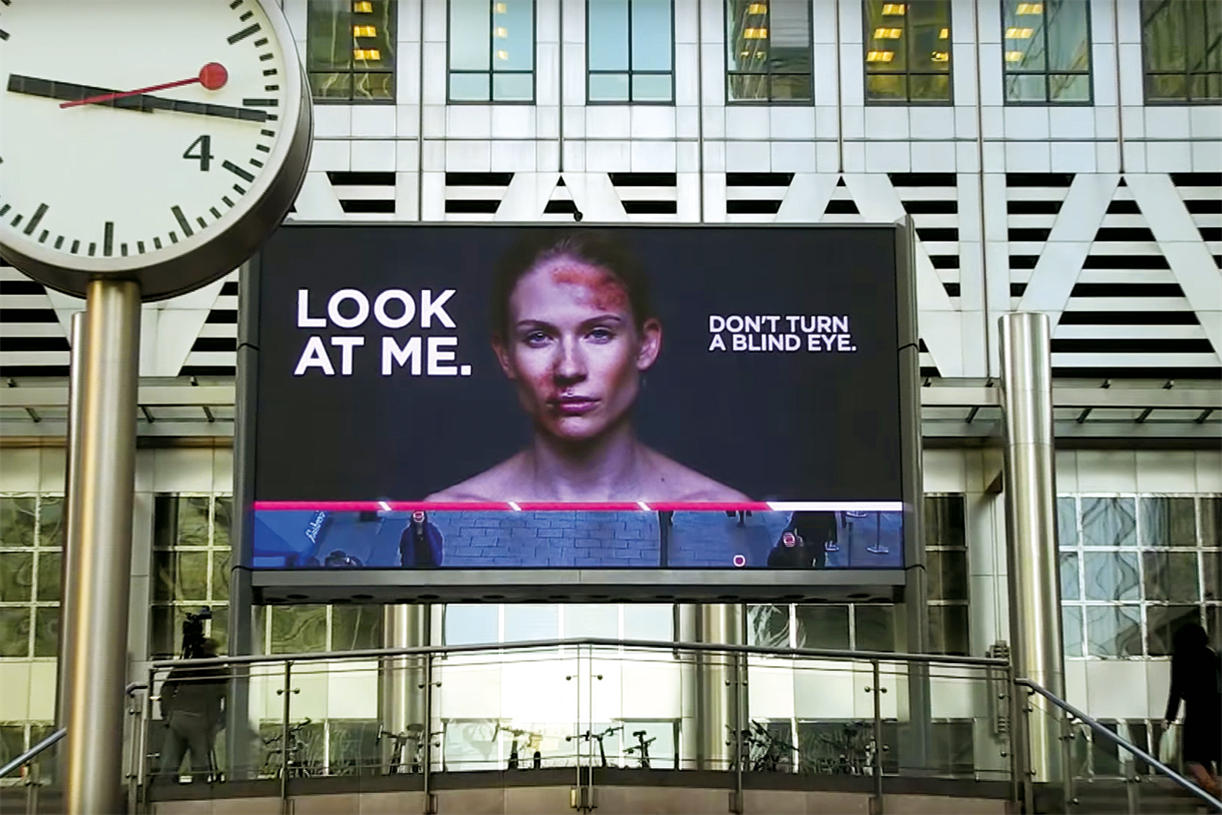 """digital billboard showing a bruised woman with the text """"Look at me"""" and """"Don't turn a blind eye."""""""