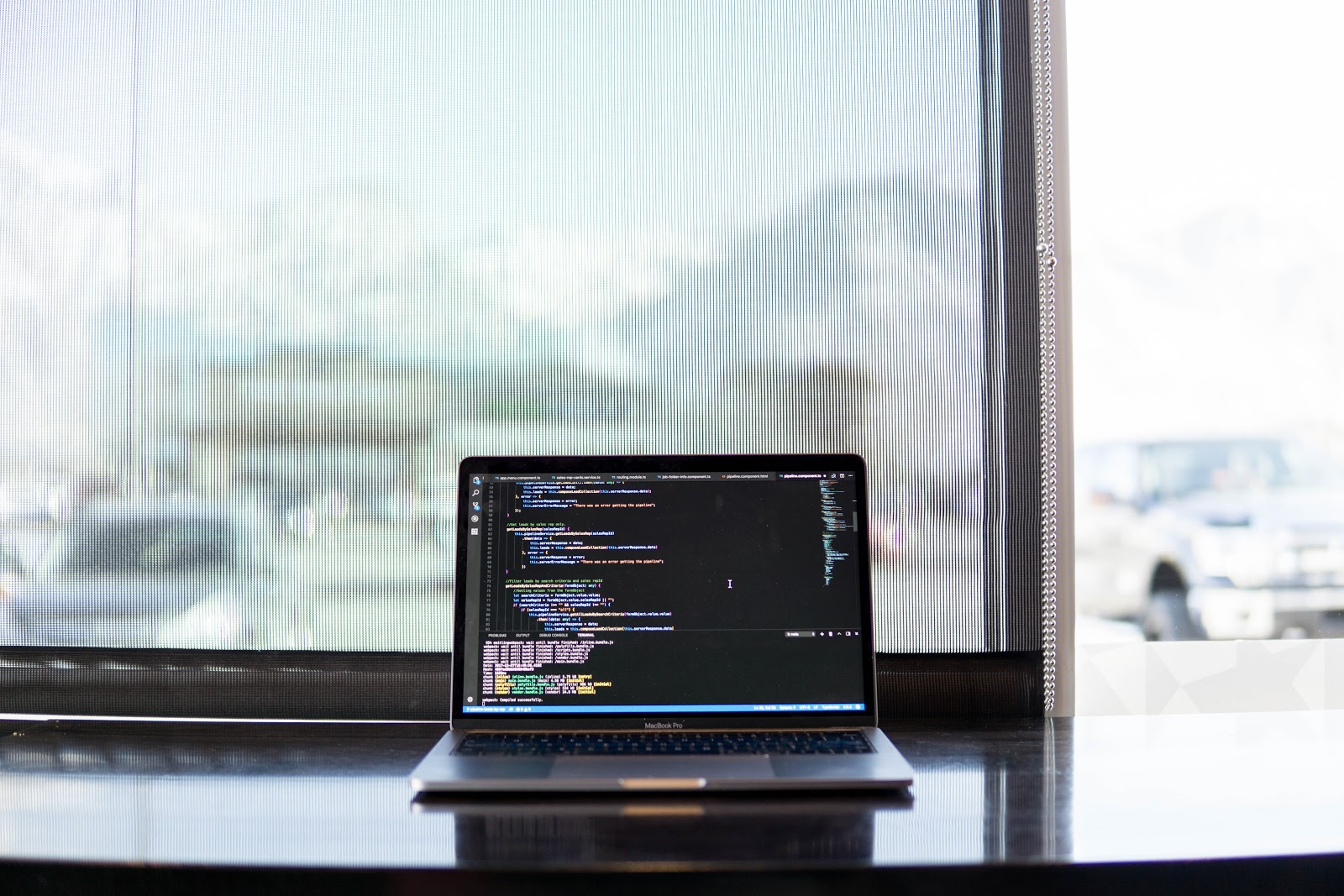 Laptop displaying a black screen with code, sitting on a black desk against a window