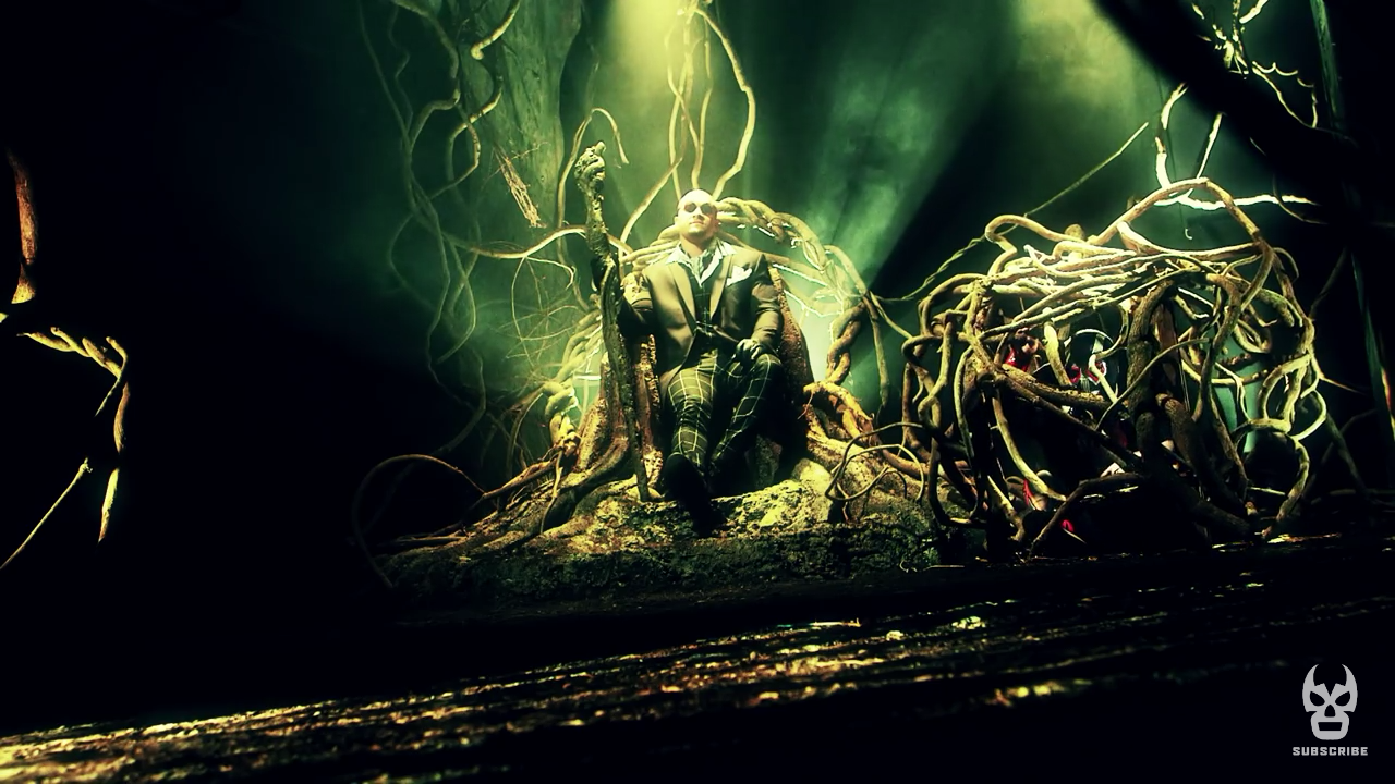 Screen cap from Lucha Underground. Killer Kross, a white man with a clean-shaven head, is wearing sunglasses and a suit and clutching a knobby stick. He's sitting on a throne made of twisted tree branches in an eerie green forest and to his right is a ball of twisted up tree branches housing a prisoner, another luchador.