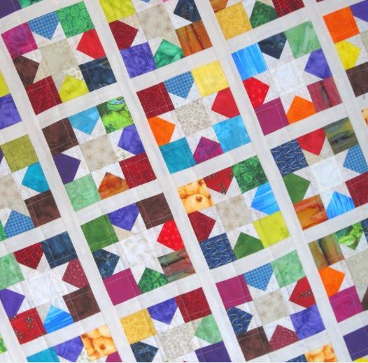 Colorful Quilt Featuring White Stars and Lines