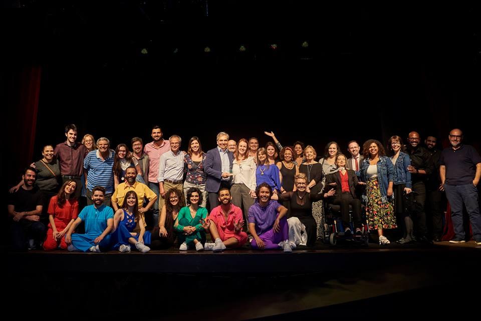 Descrição: todo o elenco, realizadores/as, parceiros/as, apoiadores/as e equipe da Escola de Gente no palco, olhando e sorrindo para a foto.