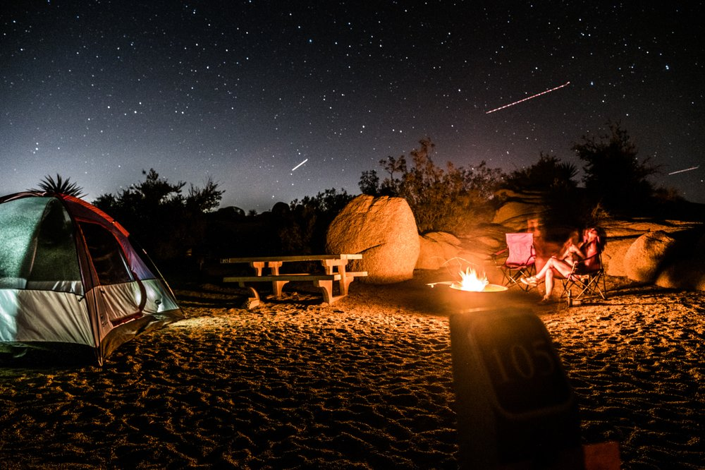 A tent, campfire and a picnic table under a sky of shooting stars