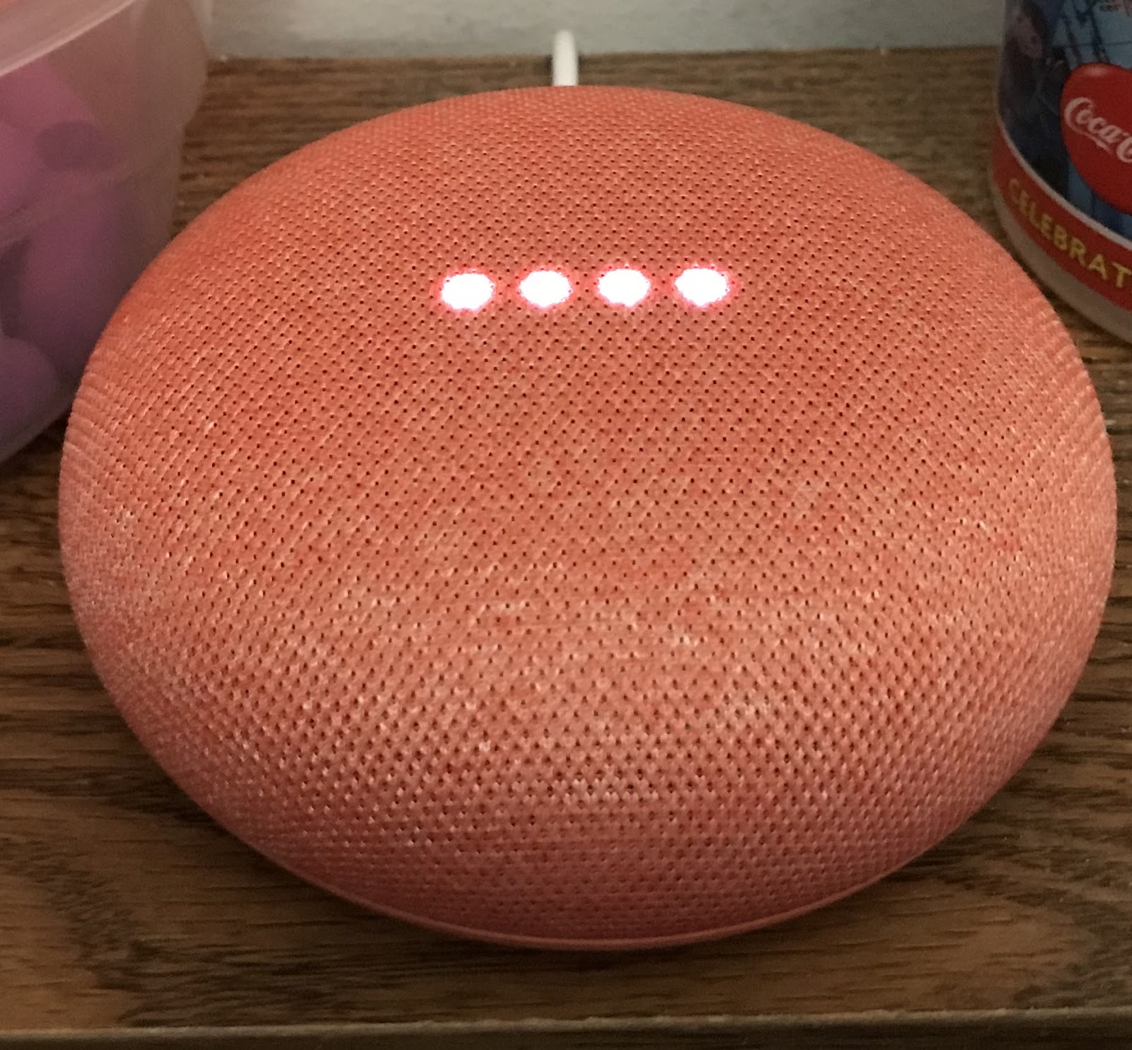 Orange colored Google Home with LED lights glowing in the middle