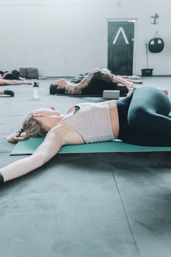 Women on mats doing the lying twist with legs bent to one side and arms outstretched.