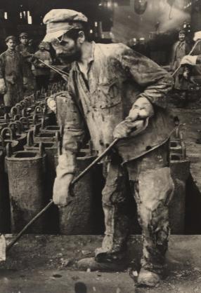 black and white photo of man shoveling