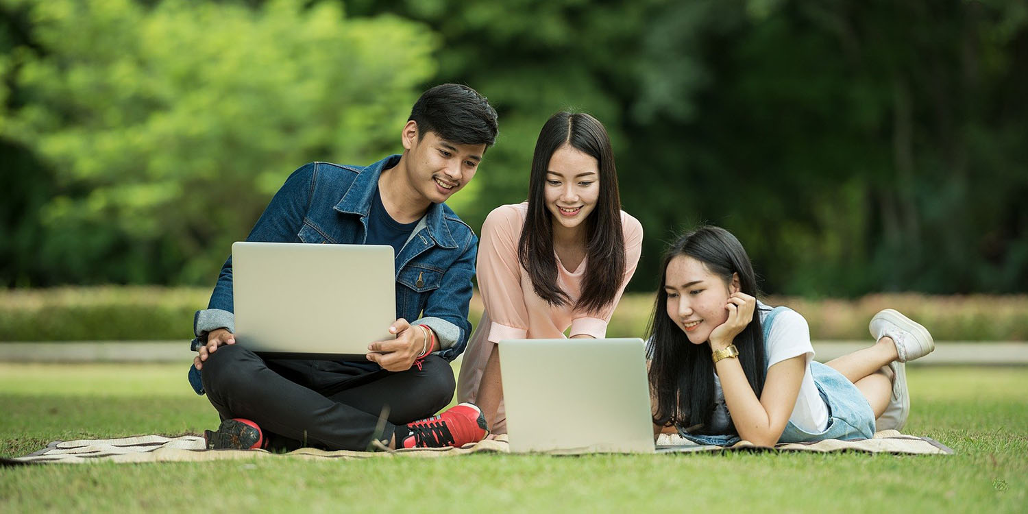 Three students studying on their laptops on a green lawn.