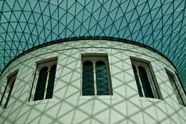 The white wall and glass roof of the central hall of the British Museum, a free museum in London.