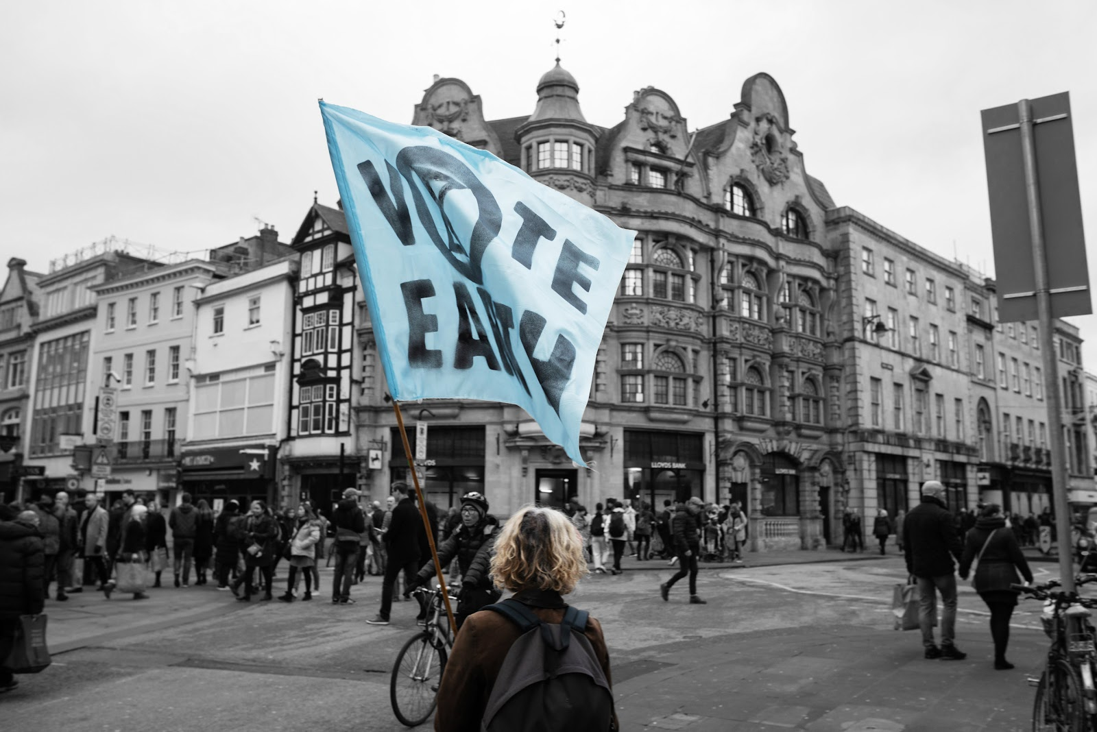 "A Rebel standing in Oxford city centre with a blue XR ""Vote Earth"" flag."
