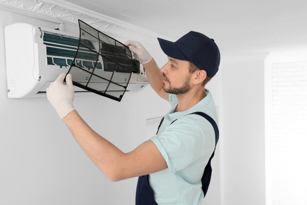 Um técnico consertando um ar condicionado.