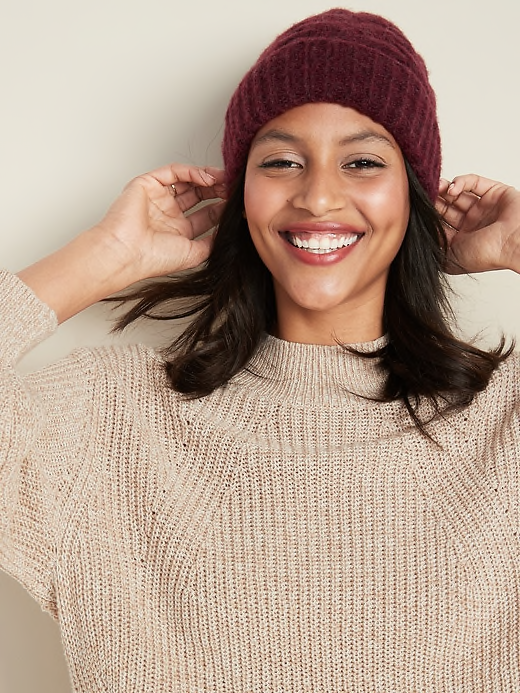 individual posing while wearing a burgundy beanie