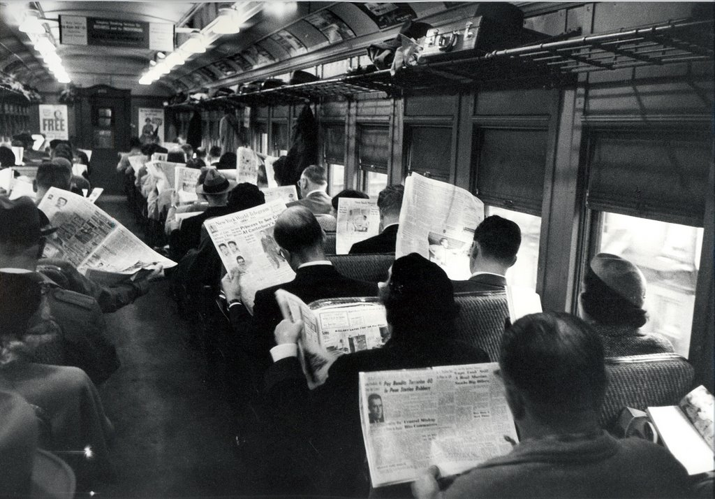 Un gruppo di persone legge quotidiani cartacei su un treno, evitando di parlare con gli altri.