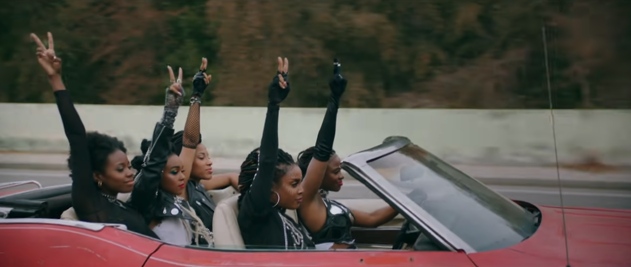 A side shot of a red convertible hovercar with 5 Black women in it, all with an arm raised and the peace symbol made with their fingers on their raised arms.
