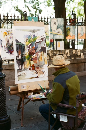 sitting man painting in front of fence with hanged paintings