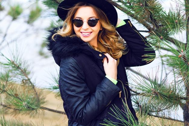 Outdoor lifestyle winter portrait of pretty playful smiling girl posing near spruce wearing vintage sunglasses retro hat and trendy parka. Free Photo