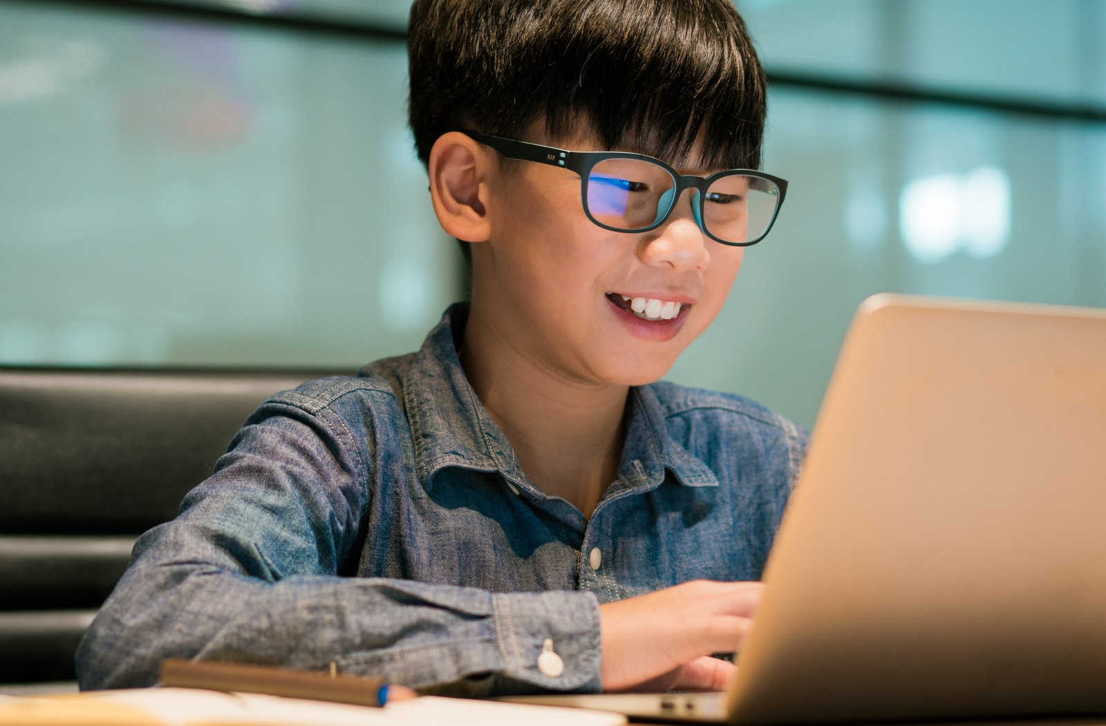 Pre-teen asian boy wearing dark rimmed glasses and denim shirt smiling while staring at his laptop computer on his desk