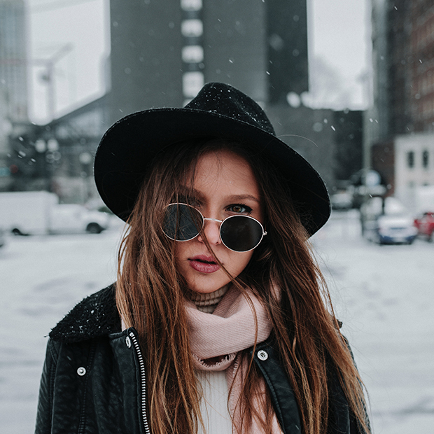 Stock image of woman in hat and sunglasses against blurred snowy city background