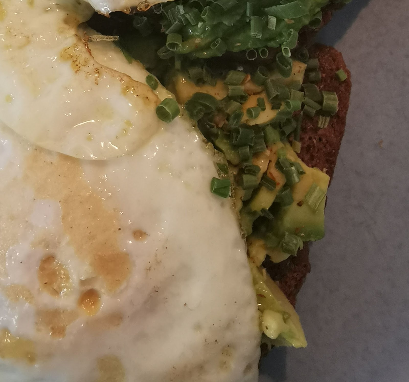 a fried egg sitting on top of mashed avocado on rye toast, sprinkled with chives