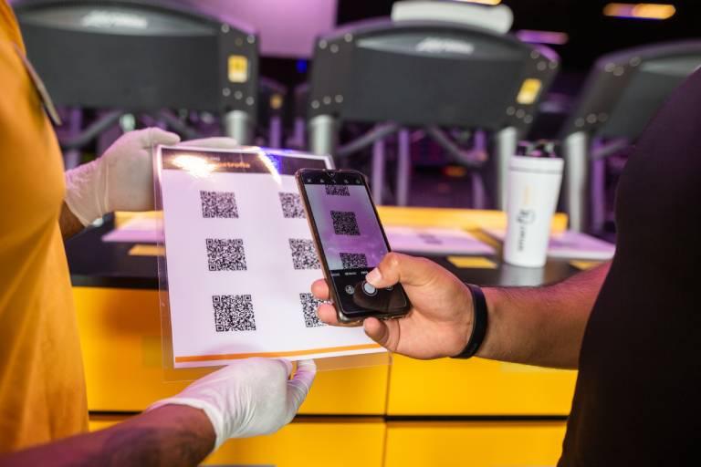 Usuario de un gimnasio de Smart Fit copiando el codigo QR de una rutina de entrenamiento en su celular.