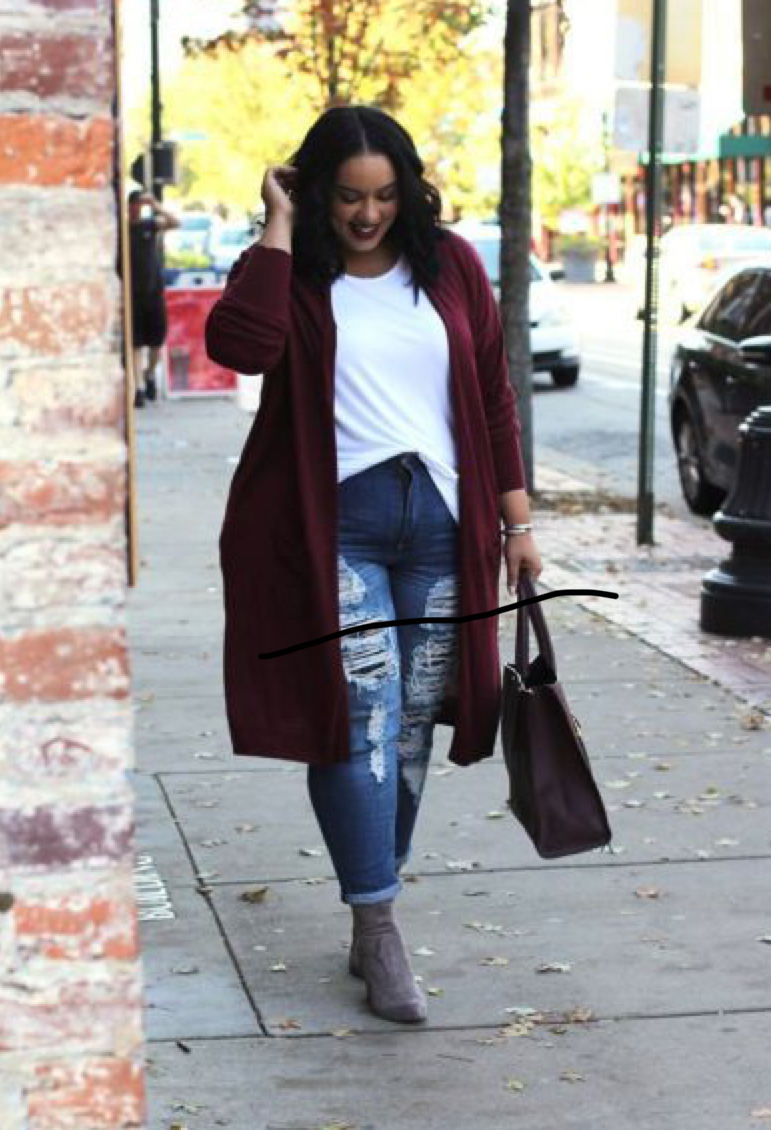 A woman is walking and wearing a dark red cardigan