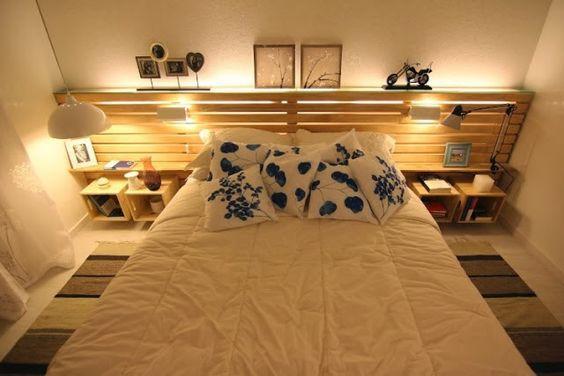 Quarto com cama de casal com cabeceira de pallet com luminárias, nichos de madeira  e objetos decorativos.