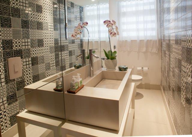 Lavabo com pastilhas com estampas maiores em tons marrons, pia de mármore neutra e piso porcelanato neutro.