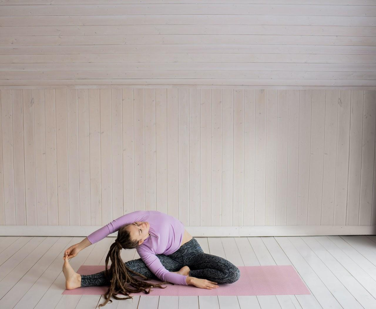 a flexible yogi stretching on a pink yoga mat