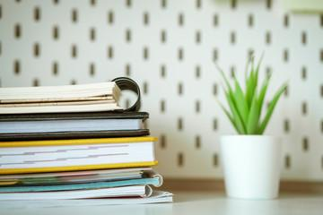 Desktop stack of notebooks and  flower in the background, soft focus
