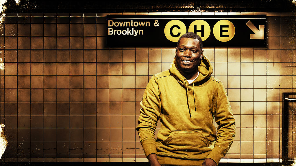 Michael Che in front of a subway station