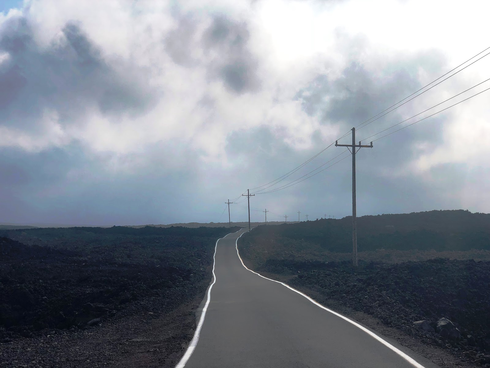 Climbing Mauna Loa by bike - Mauna Loa Observatory Road - roadway and telephone poles with lava field