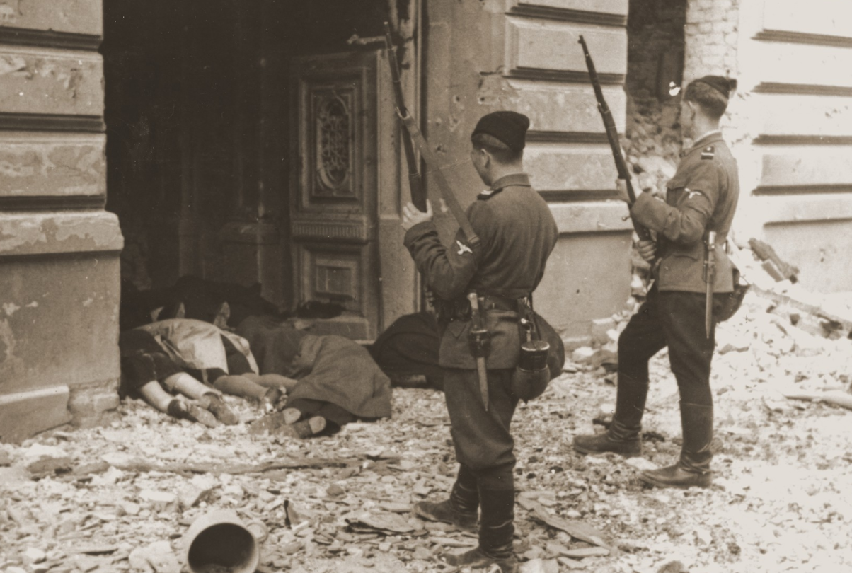 Askari or Trawniki guards peer into a doorway past the bodies of Jews killed during the suppression of the Warsaw ghetto uprising. From the United States Holocaust Memorial Museum: https://collections.ushmm.org/search/catalog/pa3281