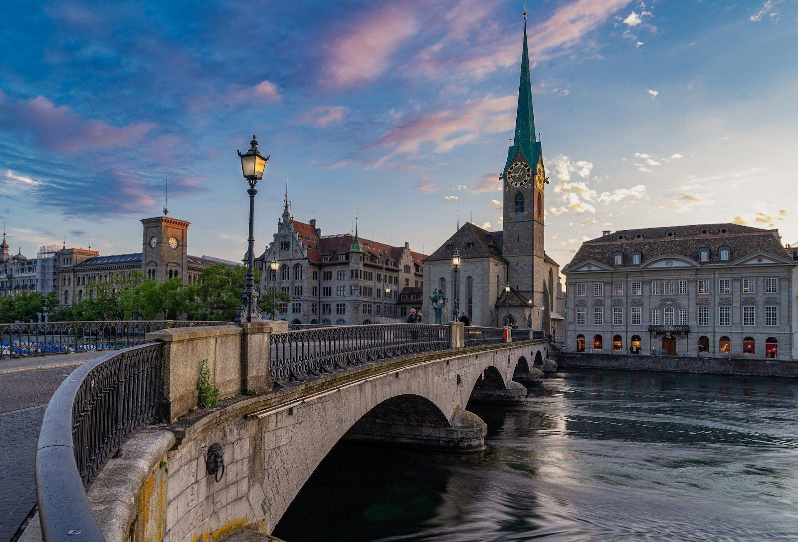 zurich bridge over river into traditional district old town medieval buildings and historical tall church during sunset