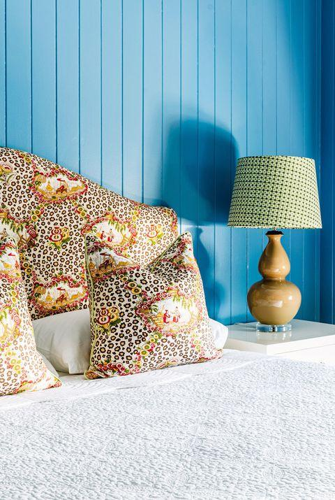 blue bedroom with leopard and floral print pillows