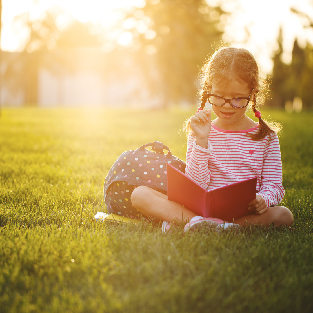 Girl reading on the grass.