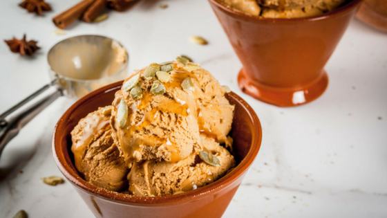 A dish of icecream with topping and nuts