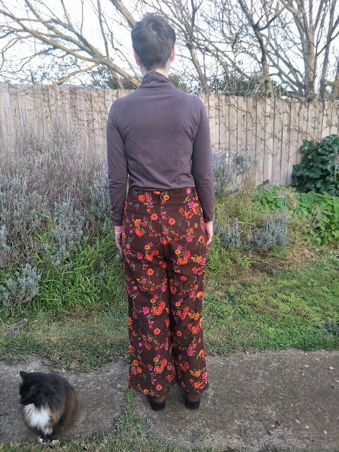 Siobhan stands in front of a garden fence. She wears a brown turtleneck long sleeve top, brown with orange and pink floral print wide leg high waisted pants, brown block heel boots, and tortoiseshell glasses. She is accompanied by a black and white cat, and has her back facing the camera to show the fit of the pants..