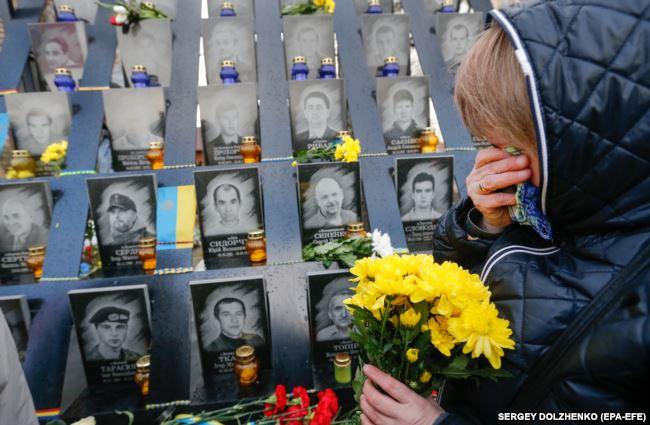 Девушка приносит цветы к мемориалу на Аллее героев небесной сотни в Киеве