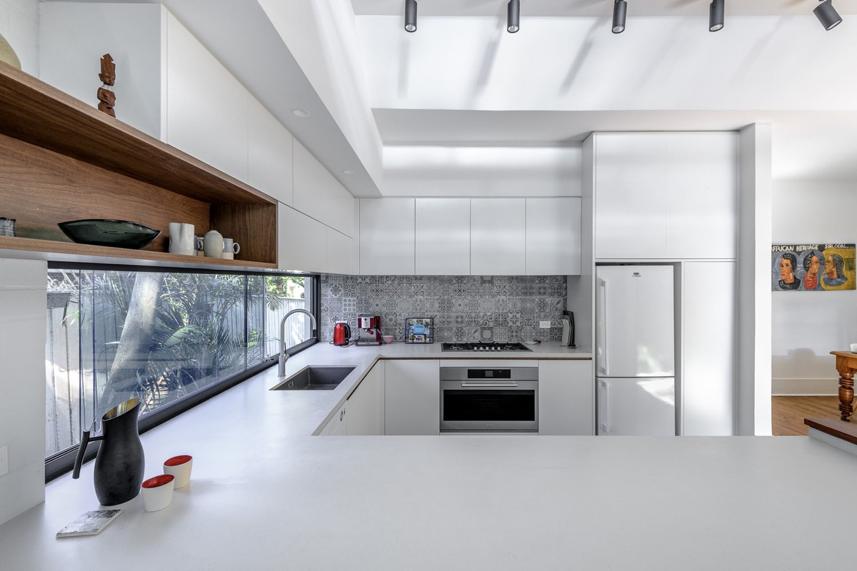 natural lit modern u-shaped kitchen featuring white flat panel cabinets, open layout design, large horizontal window above the sink and a patterned tile backsplash