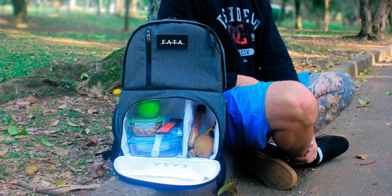 homem sentado no chão com sua mochila com compartimento térmico aberto para destacar a capacidade de alimentos transportados dentro dela