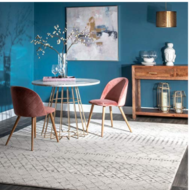 Small table with two pink chairs on white carpet in blue room